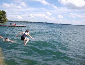 Girl jumping into lake