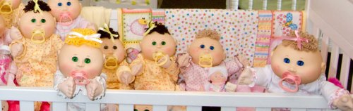 A group of Cabbage Patch dolls in a crib
