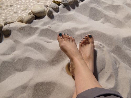 A pair of bare feet in the beach sand.