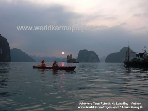 Photo of kayakers at sunset on Ha Long Bay, Vietnam