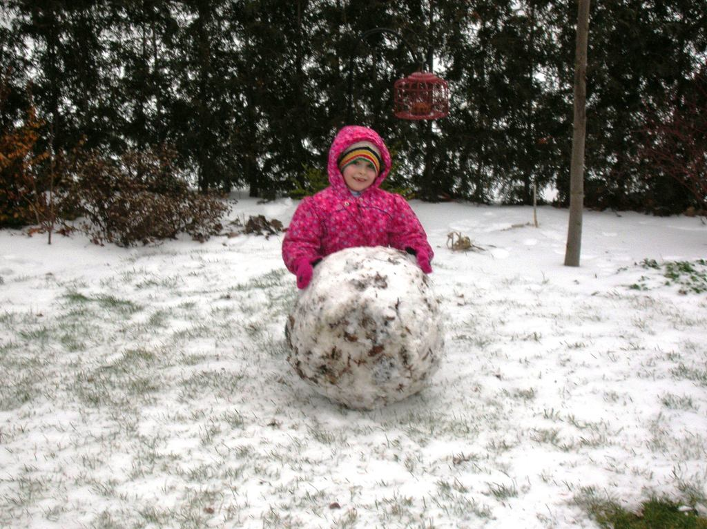 Small girl in a back yard with a giant snowball.