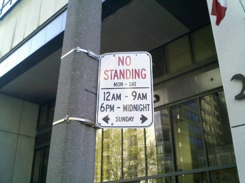 A photo of a no-standing sign on a post