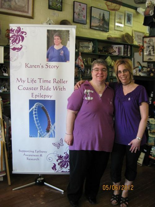 Karen and Sylvie stand beside book poster.