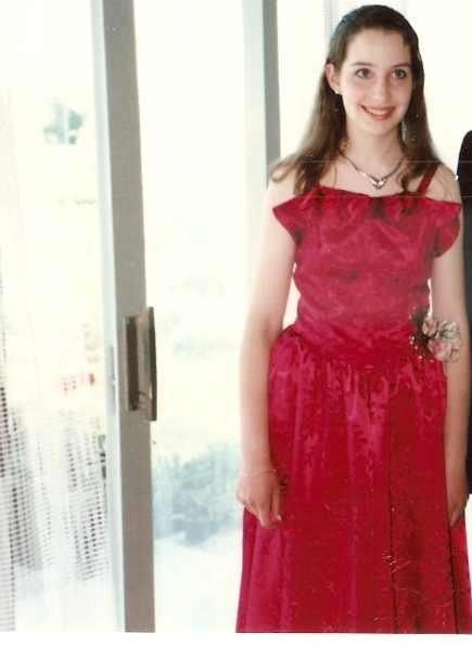 Lisa as a teenager in a red prom dress.