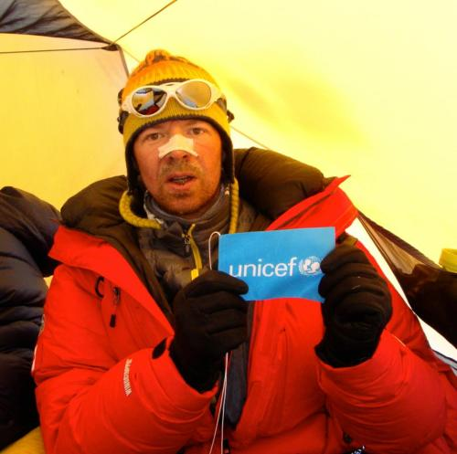 Sven inside a tent at high camp, holding a UNICEF sign