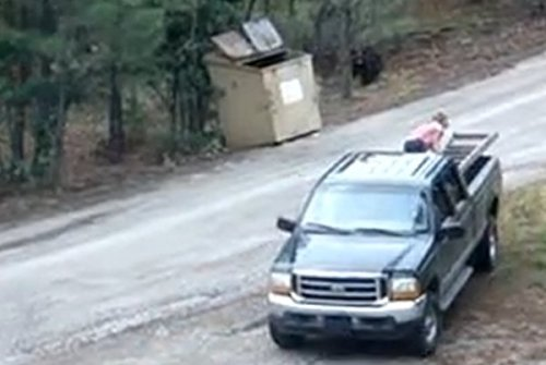 Screen shot of bear rescue video showing dumpster, truck, woman and ladder